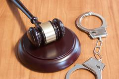 Judicial hammer and handcuffs - stock photo