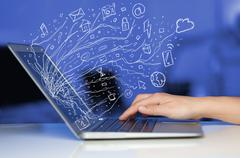 Man pressing notebook laptop computer with doodle icon cloud symbols - stock photo