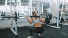 Sexy girl doing squats with a barbell in gym Stock Footage