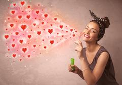 Pretty young girl blowing red heart symbols - stock photo