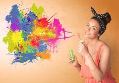 Cute girl blowing colorful splash graffiti - stock photo