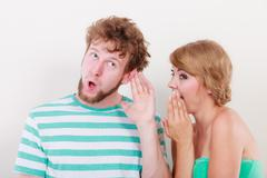 Woman telling an astonished man some secrets - stock photo