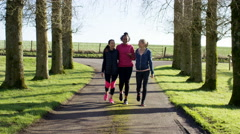 4K Female friends in fitness clothing walking together outdoors in countryside Stock Footage