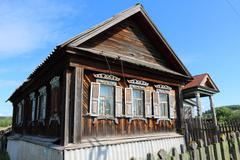Very old wooden house in the remote Russian village in the summer against a b Stock Photos