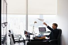 Successful Man Office Worker Daydreaming Throwing Paper Airplane - stock photo