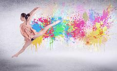 Modern street dancer jumping with colorful paint splashes - stock photo
