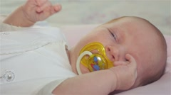 Sleepy baby sucks pacifier Stock Footage