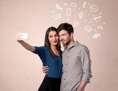 Couple taking selfie with thoughts illustrated - stock photo