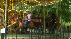 Children having fun on a marry-go-round in London Stock Footage