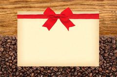 Postcard with red bow on roasted coffee beans and wooden background - stock photo