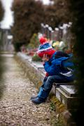 Sad little boy, sitting on a grave in a cemetery - stock photo