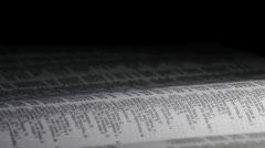 Page of phone book with names and address rotating in a black background Stock Footage