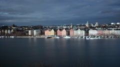 View of Stockholm lit with the sun with heavy dark clouds, Sweden - stock footage