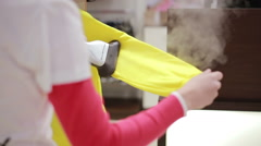 Seller irons clothing by steam iron in the store - stock footage