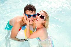 Couple with sunglasses in swimming pool. Summer, sun, water - stock photo