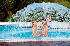 Couple in swimmning pool under splashing fountain. Summer heat - stock photo