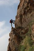 The climber with a backpack climbs on a steep rock Stock Photos