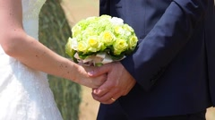 Married couple holding hands with yellow bouquet. Stock Footage