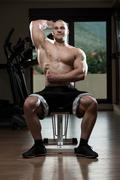 Young Bodybuilder Exercise Triceps In The Gym - stock photo