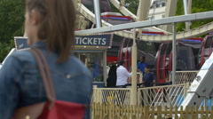 Tourists waiting to get on a ferris wheel in London Stock Footage