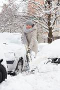 Independent woman shoveling snow in winter. - stock photo