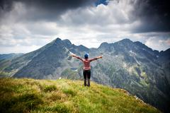 Woman hiker relaxing on a top of a mountain admiring surrounding rocky peaks Stock Photos