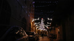 Small street in old Jerusalem decorated with Christmas lights, nighttime Stock Footage