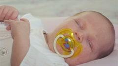 Sleepy baby sucks pacifier Stock Footage