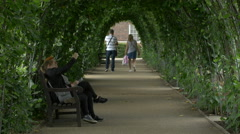 People walking under a green arch in London Stock Footage