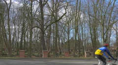 Cyclist Cars Near Old Cemetery Along a Road Sunny Day Tombstones Graves Burial Stock Footage