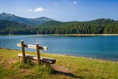 Wooden bench at Black Lake in Durmitor, Montenegro - stock photo