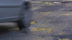 Vehicle is Driven by Puddles Car's Wheels Bumper Water in a Puddles Unrepaired Stock Footage