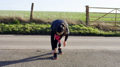 4K Young woman out for a run in the countryside tying up her laces - stock footage