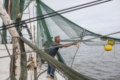 Commercial fishermen pulling nets Stock Photos