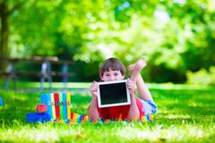 Student child with tablet computer in school yard - stock photo