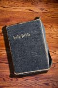 Old Rugged Holy Bible on Wood Texture Background - stock photo