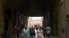 People walking under a railway bridge in London Stock Footage