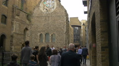 Adults and children walking by Winchester Palace in London Stock Footage