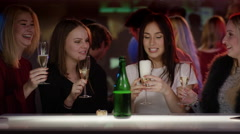 Beautiful girls glink their glasses at bar Stock Footage