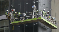 Workers with vests and helmets working on a scaffolding in London Stock Footage
