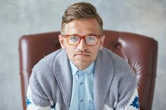 Portrait of a stylish intelligent man with glasses stares into the camera, go Stock Photos