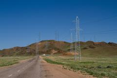 Country road and Power Transmission Line. - stock photo