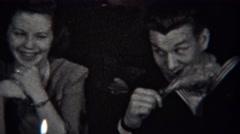1943: Navy sailor man slyly eating turkey leg makes girlfriend laugh. STATEN Stock Footage