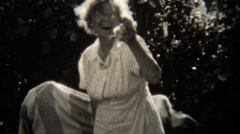 1943: Crazy grandma holding up chickens passing them out to grandpa. STATEN Stock Footage