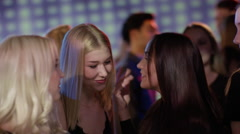 Attractiv girls whispering to each other on dancefloor Stock Footage