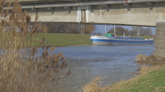 Blue Ship is Parked a the River Bank Concrete Bridge on a Supports Rippling Stock Footage