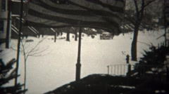 1944: American flag waves in snow covered wealthy residential neighborhood.  Stock Footage