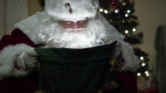 Santa Claus looks in his magical bag of toys and smiles at the camera - stock footage