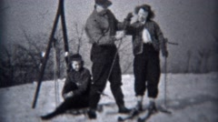 1944: Man dresses women for 1st skiing down small local hill after snowstorm. Stock Footage