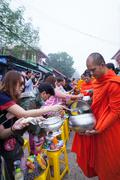 SANGKHLABURI, THAILAND - DECEMBER 27, 2015: Traveler crowd make merit with mo Stock Photos